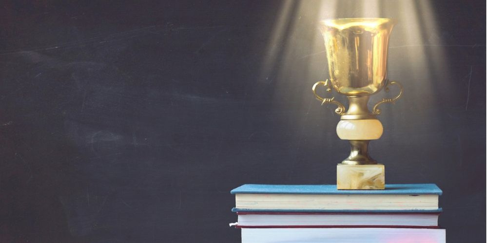 golden-trophy-on-pile-of-books-against-blackboard-with-sun-rays-over-picture-id908745612 (1).jpg